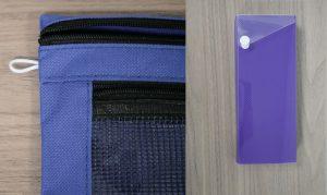 Blue canvas pencil case next to a purple hardshell pencil case
