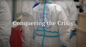 """Healthcare worker facing away from the camera with the text """"Conquering the Crisis"""""""